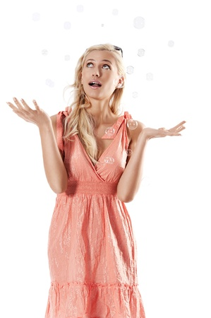 pretty young blond woman wearing a summer orange dress standing against white background  looking towards the soap bubbles photo