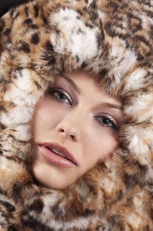 fashion close up portrait of a young pretty girl with a fur all around her face  photo