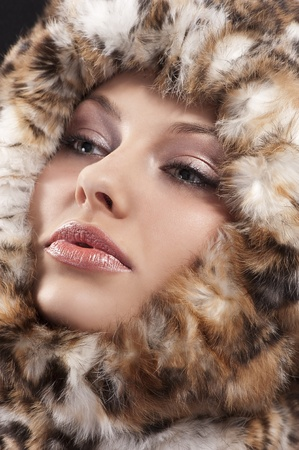 fashion close up portrait of a young pretty girl with a fur all around her face looking on one side Stock Photo