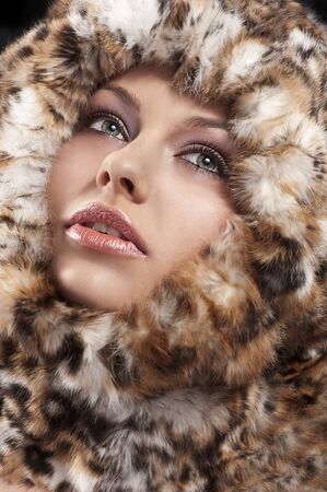 fashion close up portrait of a young pretty girl with a fur all around her face woman photo