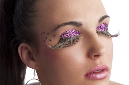 closeup on the face of beauty brunette with long false eyelashes and creative make up with colored gem stone photo