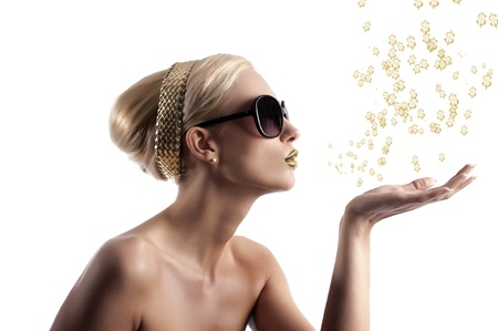 blond young woman in beauty shot looking on one side and blowing some golden star from her hand photo