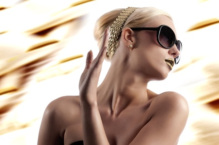 fashion portrait of young blond woman with hair style gold lips and wearing sunglasses over white photo