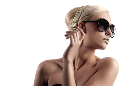 fashion portrait of young blond woman with hair style gold lips looking in one side with sun glasses  photo