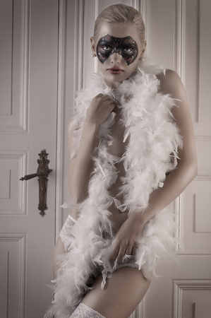 pretty blonde girl wearing a feather boa and panties posing in a doorway photo