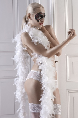 glamour shot of a sensual pretty girl posing with a featherboa, white stockings and a painted black mask on her face photo
