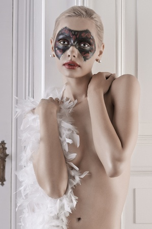 portrait of a sensual girl with a painted mask on her face and wearing just a white feather boa  photo
