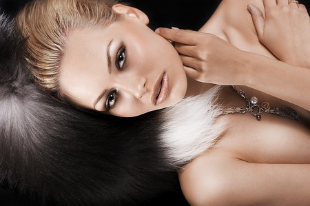 beautiful girl posing on black wearing only fur and a necklace Stock Photo - 10683523