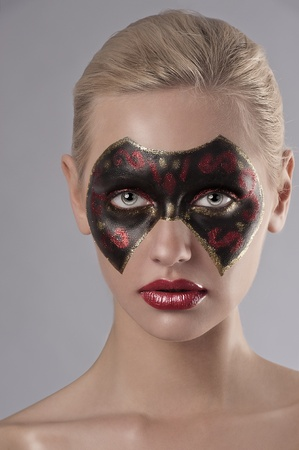 painted face mask: beauty face shot of a young woman having a black and red carnival mask painted on her face Stock Photo