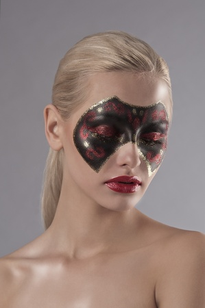 painted face mask: face shot of a pretty blonde with red lipstick and a carnival mask painted on her face