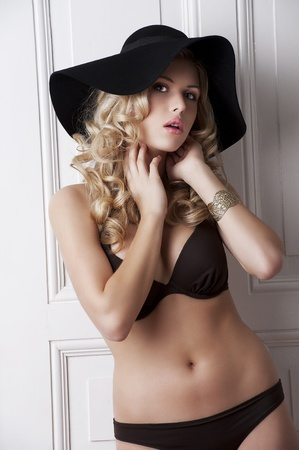 charms: fahion shot of young and cute model wearing a bikini and jewelery with blond curly hair and  black hat in old fashioned room Stock Photo