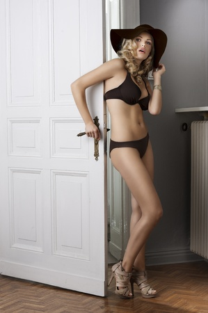 woman panties: fahion shot of young and cute model wearing a bikini with blond curly hair and hat in old fashopn room