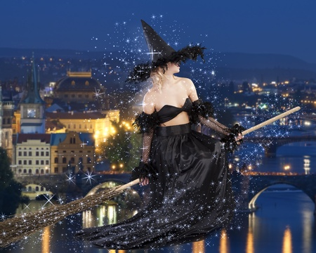witch face: young beautiful woman in witch black dress with hat and a long gown pulling face and sitting on broom Stock Photo