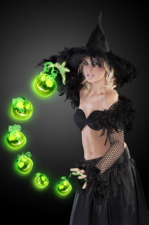 young beautiful woman in witch black dress with hat and a long gown pulling face, making a spell photo
