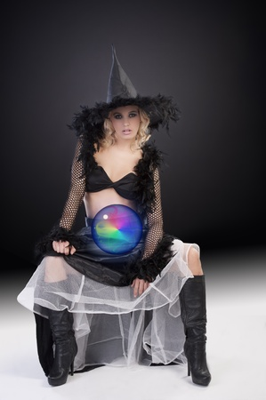 young beautiful woman in witch black dress with hat and a long gown holding a magic crystal photo