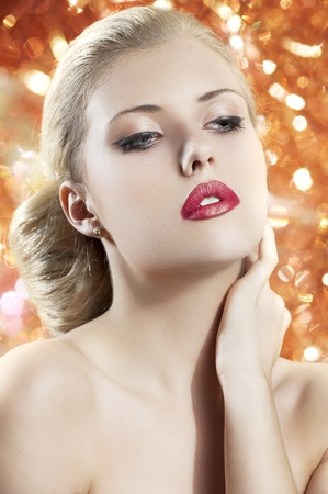 old fashion portrait of a young beautiful blond woman with hair style and deep red yellow lips on black background photo