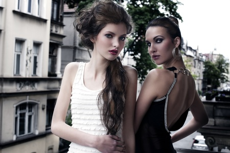 fashion shot of two attractive and elegant girl friend outside in a balcony with old fashion style building in background photo