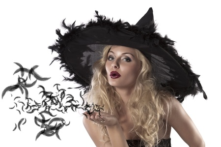 sexy witches: face shot of a cute and sexy girl dressed with a huge witch hat with feathers blowing a kiss Stock Photo