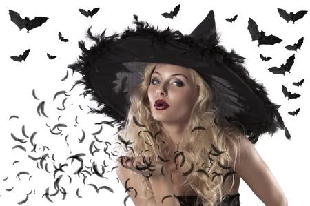 bruja: disparo de cara de una chica linda y sexy vestida con un sombrero de bruja enorme con plumas soplando un beso Foto de archivo