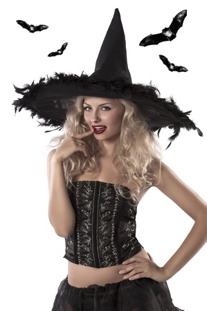 sexy girl dressed as a witch wearing a huge black feather hat and a dark corset
