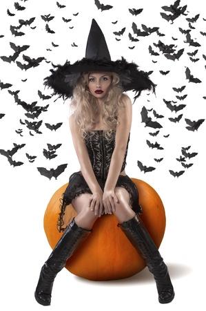 brujas sexis: bruja rubia muy sexy y atractiva con un sombrero de plumas negras y sentado en una calabaza