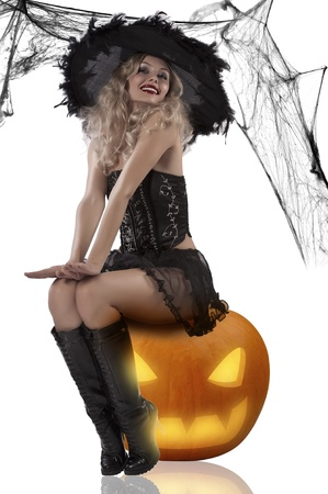 very sexy and attractive blonde dressud up as a witch wearing a black feather hat and sitting on pumpkin Standard-Bild