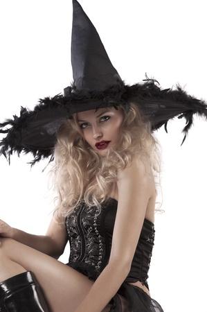brujas sexis: cerca de una hermosa chica rubia vestida como una bruja vistiendo un corsé negro y un sombrero de plumas enormes Foto de archivo