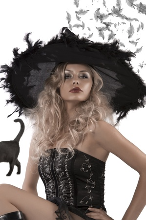 bewitch: close up portrait of a young blonde woman with a black corset and black witch hat with feathers