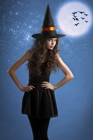 very young girl dressed as halloween witch posing under stars and moon wearing a huge witch hat photo