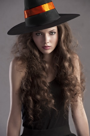 face shot of a young and beautiful girl dressed up for halloween with a huge black witch hat looking straight into the cam photo