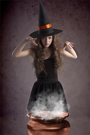 young and pretty girl dressed up for halloween with a huge black witch hat making spells behind a witchs cauldron photo