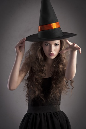cute and pretty girl with long curls posing for halloween wearing a huge black and orange hat