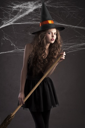 cute young model dressed up as a halloween witch wearing a huge orange black hat photo