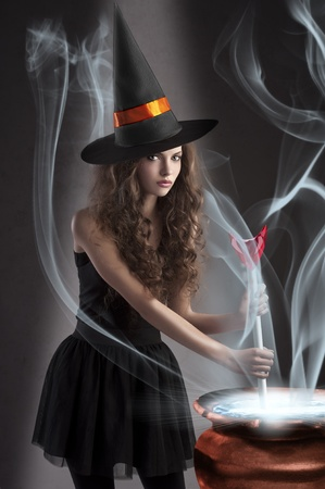 halloween shot of a young and beautiful witch wearing a huge black and orange hat making a poison in a big pot photo