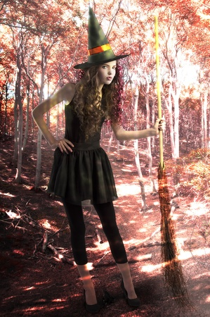 cute girl dressed as a halloween witch wearing a huge hat and holding a broom in a forest  photo