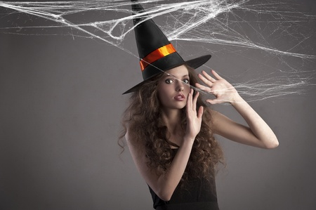 very young and beautiful witch wearing a black dress and black-orange hat making a scared face photo
