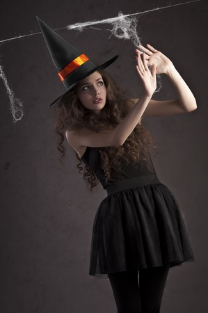 sweet and cute girl dressed as a witch with a huge black hat looking terrified photo