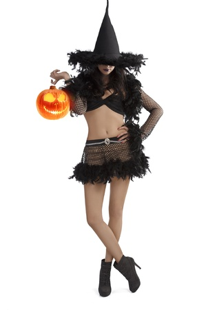 halloween mask: very pretty young brunette in black witch dress with hat and high heel ready for halloween standing with party ball against white background