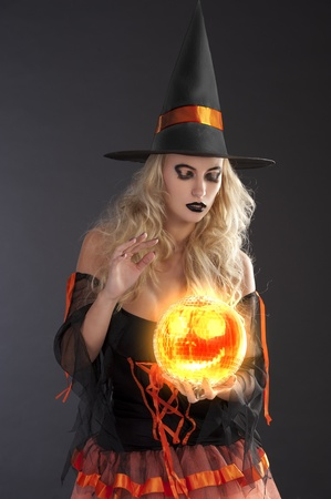 bewitch: close up of a very sensual cute blond witch in orange and black dress with hat fortune telling with crystall ball
