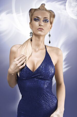 fashion shot of a blonde girl with a creative up-do and wearing a metallic blue dress photo