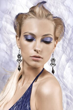 beauty face shot of a pretty blonde with an electric blue make up and fantasy up-do photo