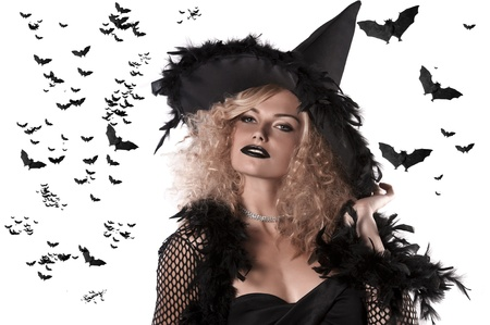 portrait of a cute and curled blonde girl dressed as a halloween witch wearing a huge black feather hat photo