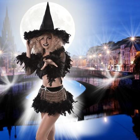 sorci�re halloween: portrait d'une jolie sorci�re de Halloween blonde et fris�e v�tu d'un costume noir � plumes faisant des sorts Banque d'images