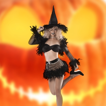 glamour shot of a cute and curled blonde posing in a black witch costume and high heels photo