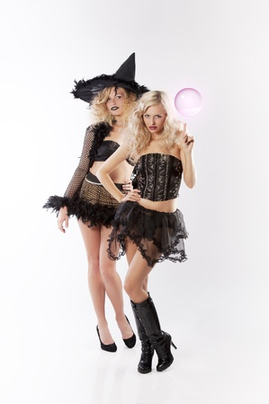 two young beautiful girls wearing witch black dress making magic with pink crystal ball