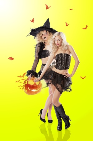 sexy halloween girl: two young beautiful girls wearing witch black dress and jack o lantern ready to fly Stock Photo