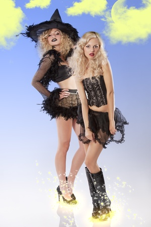 two young beautiful girls wearing witch black dress ready to party Haloween together photo