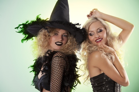 two young beautiful girls wearing witch black dress making party photo