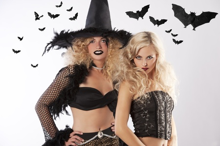 two young beautiful girls wearing witch black dress ready for black magic photo
