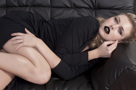 fashion shot of a beautiful blonde girl with black lipstick laying on a black leather sofa photo